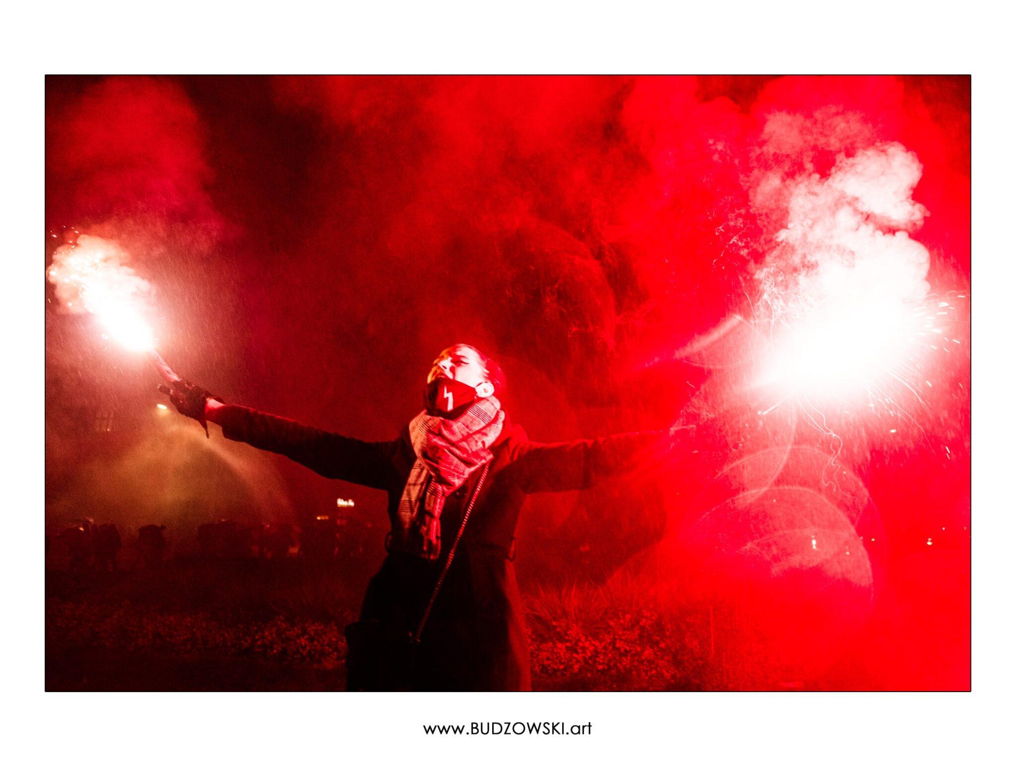 Gabriela Wiśniewska trzymając race krzyczy To jest wojna! Zdjęcie wyróżnione w konkursie fotograficznym.